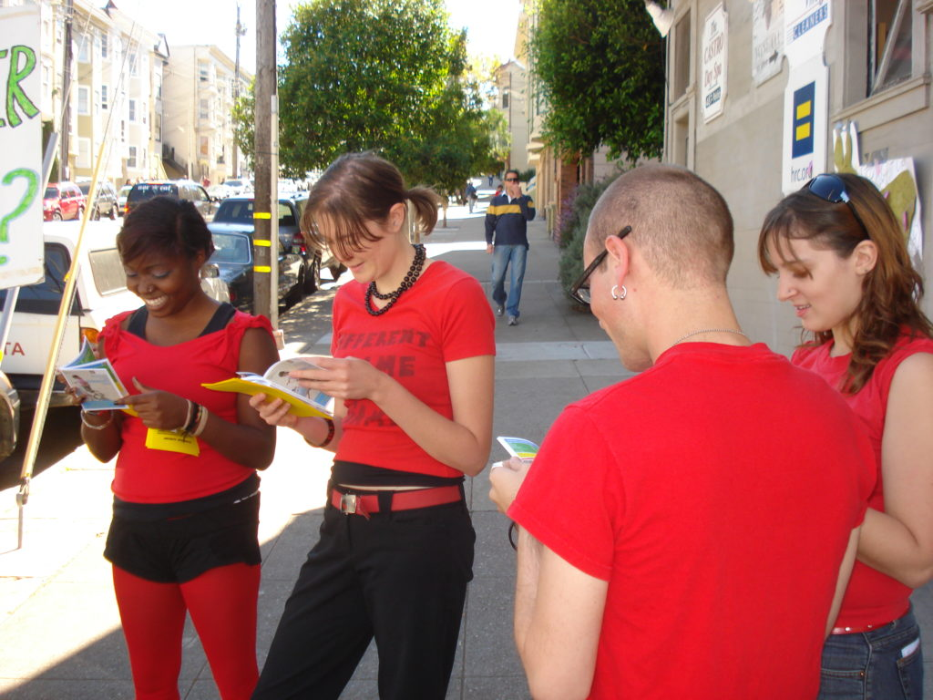 a group of radical cheerleaders scandalized by the naked corporate avarice on display in the hrc.org store official corporate ally buyer's guide while milling about at the corner of 19th and castro at the original HRC.org store location
