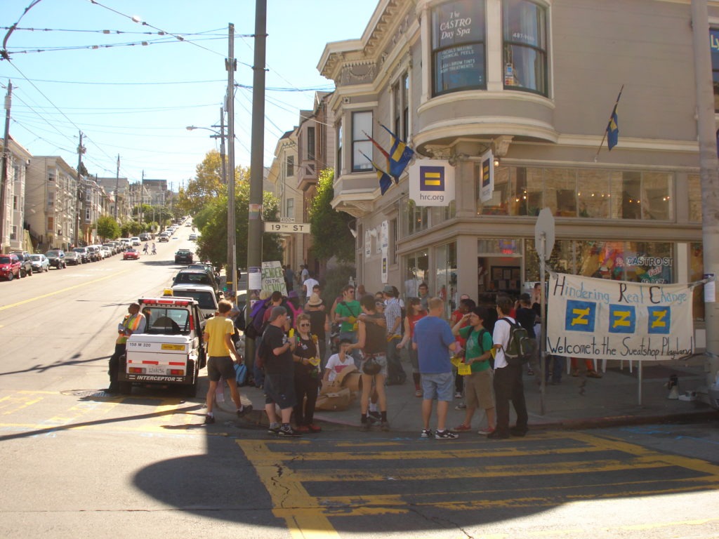 a group of people with signs and props gathered on the sidewalk at the corner of 19th and castro in front of the original hrc.org store location