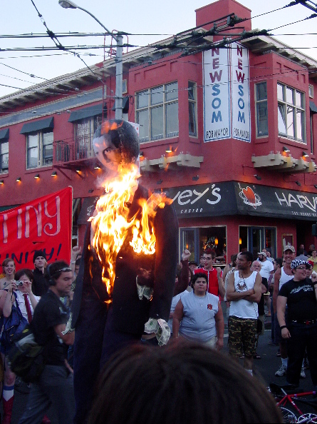 "people gather around watching the gavin newsom effigy now fully ablaze as they hold the intersection of 18th and castro directly in front of a giant ""newsom for mayor"" sign above harvey's restaurant."