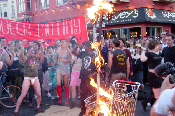 "flame eats away at the last of the effigy propped up in a shopping cart as a large crowd fills the street at 18th and castro in front of harvey's restaurant with the red ""queer mutiny..."" banner in the background"