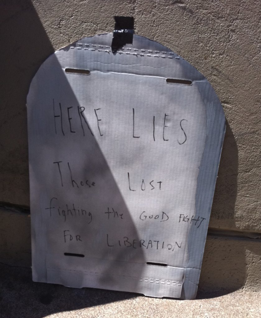 "cardboard tombstone reading ""here lies those lost fighting the good fight for liberation"""
