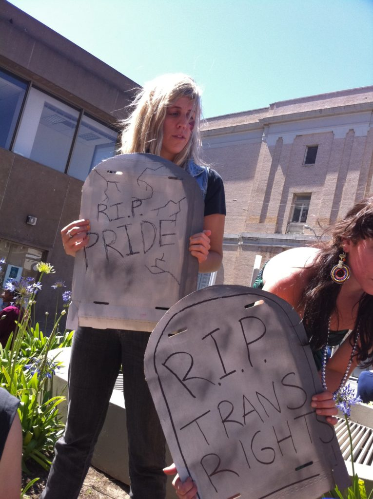 "people holding cardboard tombstones reading ""r.i.p. pride"" and ""r.i.p. trans rights"" gathered on the large concrete planter in the post office area at market and hayes"