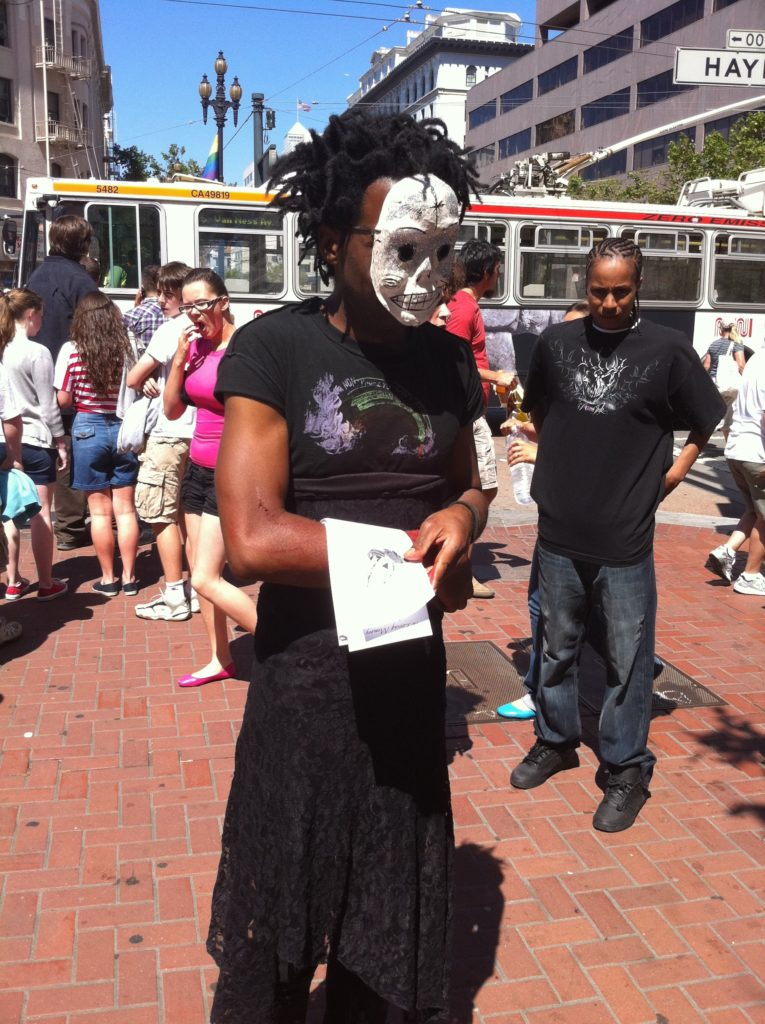 person in a sugar skull mask and a black lace skirt handing out flyers at market and hayes