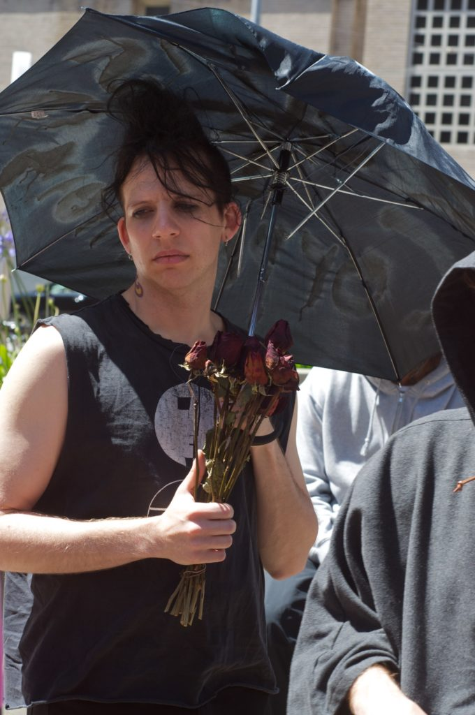 person holding dead flowers and an umbrella appearing sad
