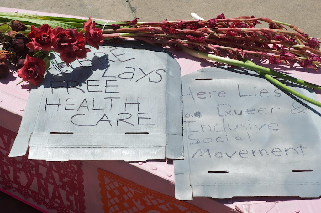 "close up of indehiscent pink gladiolis and roses and cardboard tombstones on the lid of the pink cardboard coffin that read: ""here lays free health care"" and ""here lies a queer & inclusive social movement"" and papel picados plastered on the side of the coffin"