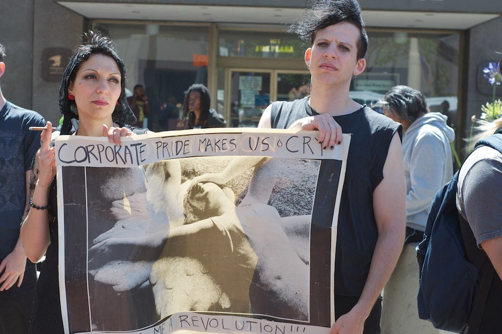 "two people with apparently dour expressions holding a sign that says ""corporate pride makes us cry"""