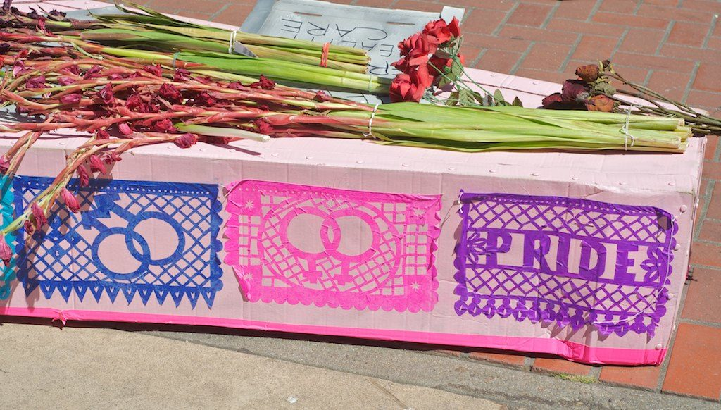 detail of a pink cardboard coffin covered with slightly wilting indehiscent pink silk stemmed gladioli and multicolored queer papel picado pasted on the side