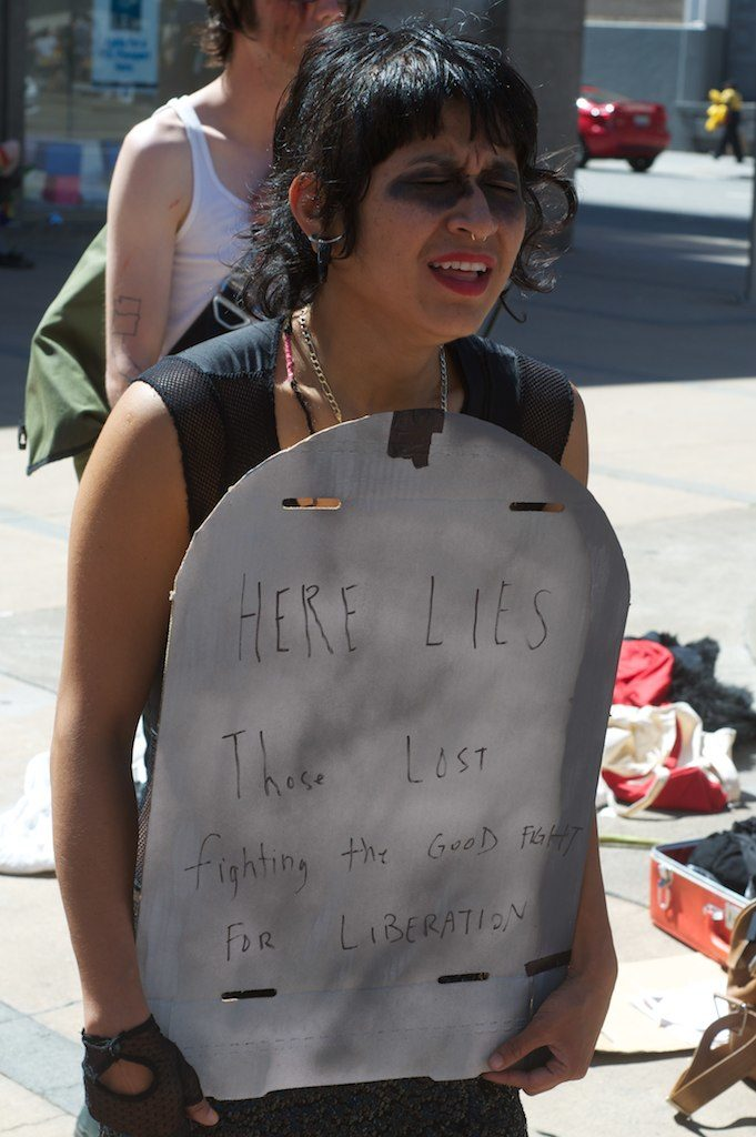 "person sobbing holding a cardboard tombstone reading ""here lies those lost fighting the good fight for liberation"""