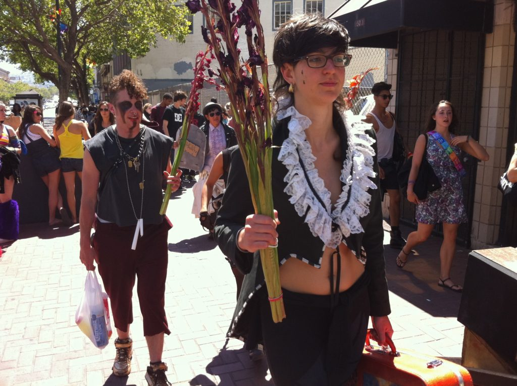 the procession continues with a person walking down market holding a few rubber-banded stems of wilted violet hyacinth