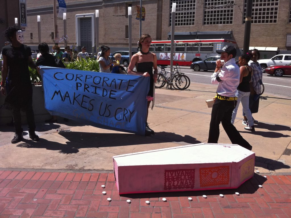 "two people holding a blue ""corporate pride makes us cry"" banner next to a pink cardboard coffin with tealight candles dotting its perimeter at the corner of market and hayes"