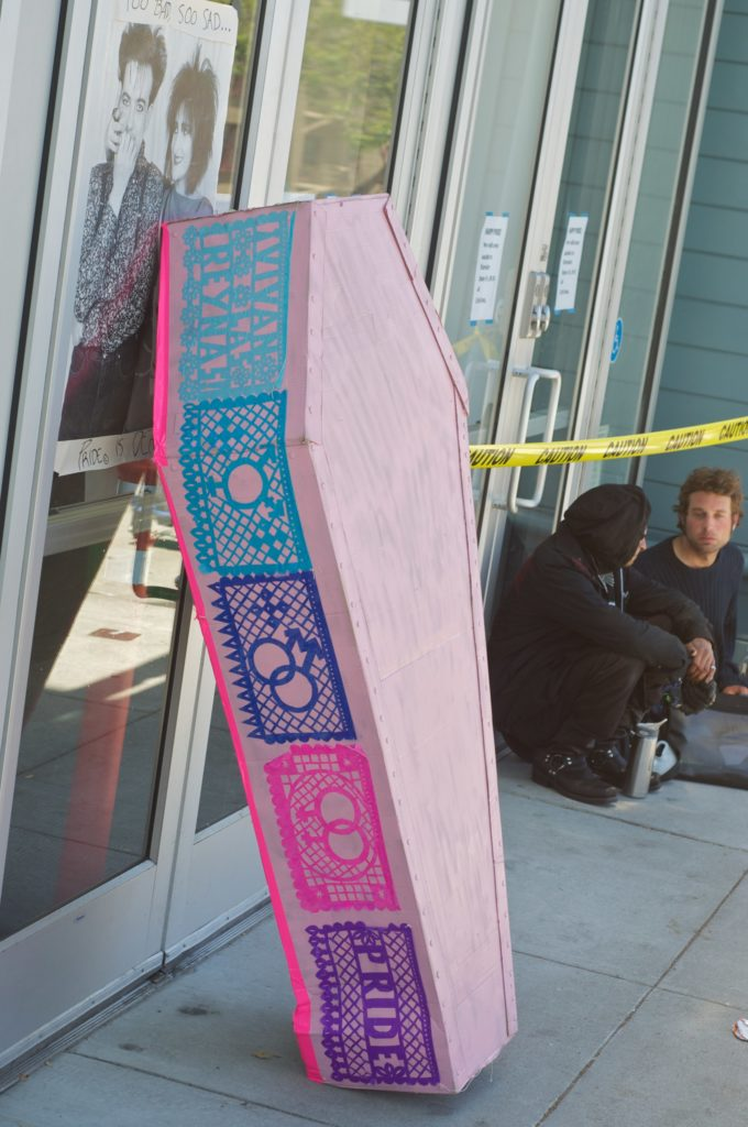 pink cardboard coasted plastered with queer multicolor papel picado leaning against the front entrance of the lgbt center