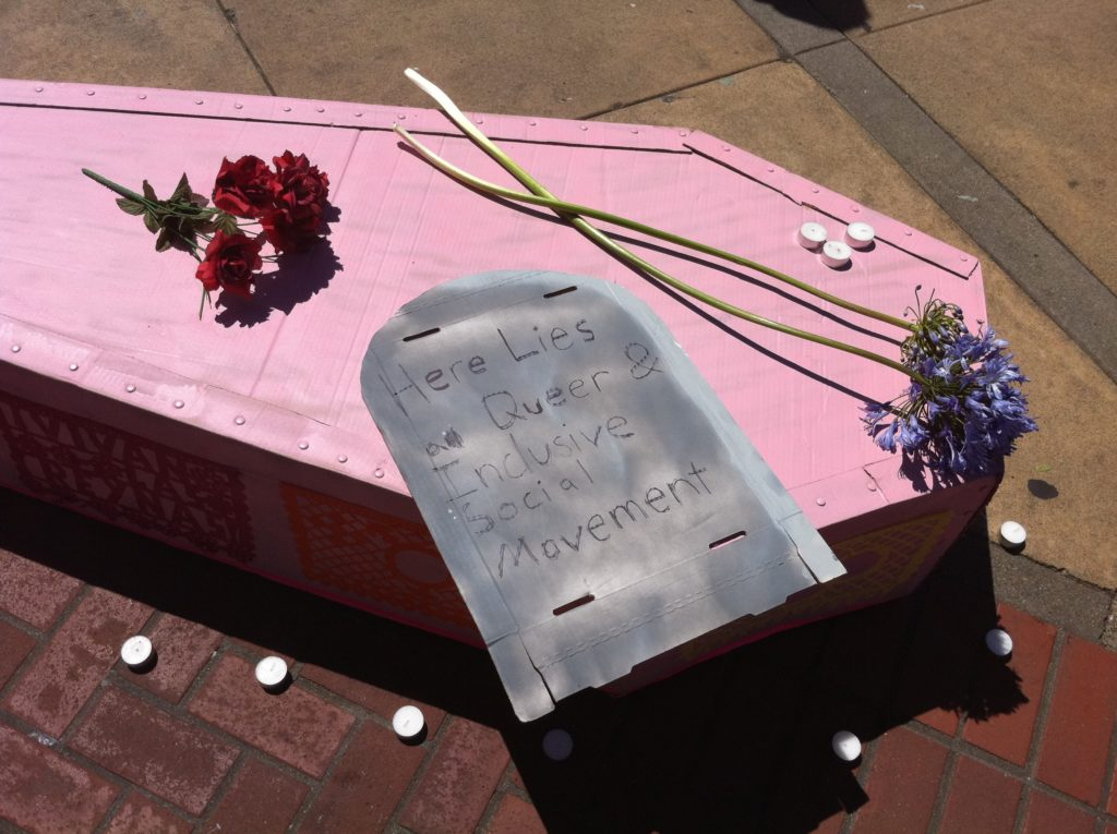 "tealight candles dot a nosegay of red roses and two stems of violet hyacinth and a cardboard tombstone reading ""here lies a queer & inclusive social movement"" on the lid of a pink cardboard casket"
