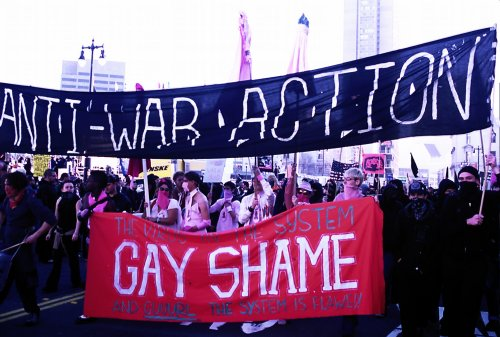 "a crowd of people forming a black bloc with a large black banner reading ""anti-war action"" and underneath a red ""gay shame"" banner"