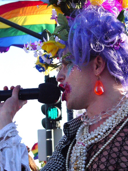 close up of a speaker with a microphone providing detail of their elaborate clothes, make-up, wig with flowers and jewelry. the pride flag looms in the background