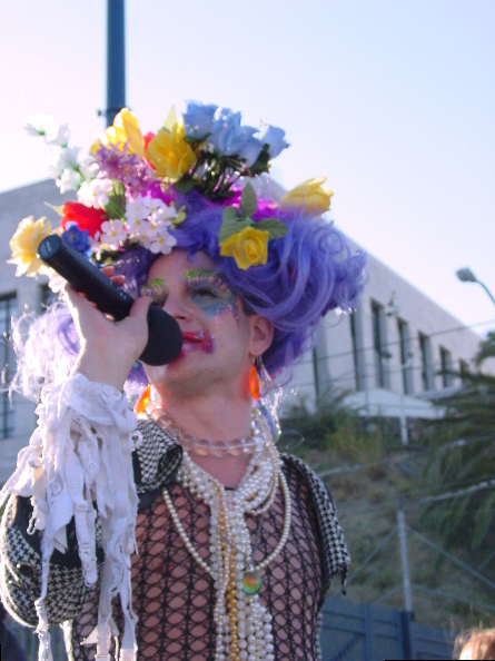 another shot of the same elaborately dressed speaker with flowers in their purple wig, with the u.s. mint in the background