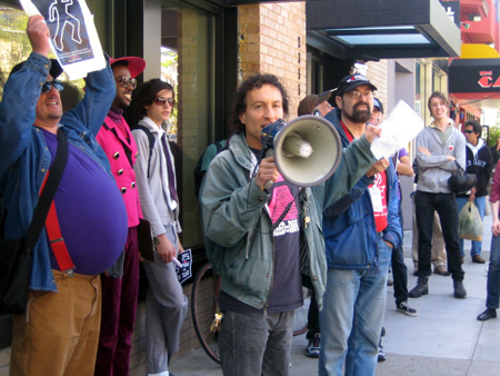a person with a bullhorn with a group of people rallying on the sidewalk in front of the coldwell banker office on market near castro