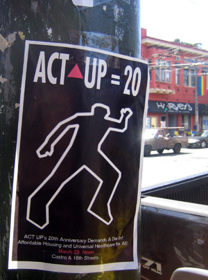 an act up 20 poster taped to a muni pole at 18th and castro with the awning of harvey's restaurant visible in the background