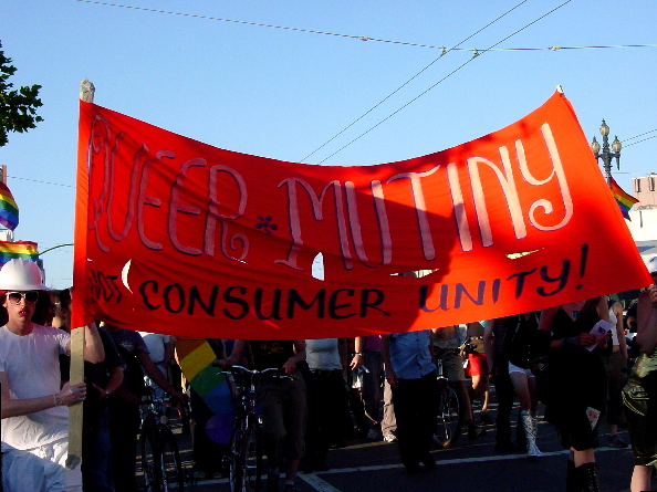 "the procession led by the red ""queer mutiny not consumer unity"" banner continues as the sun goes down"