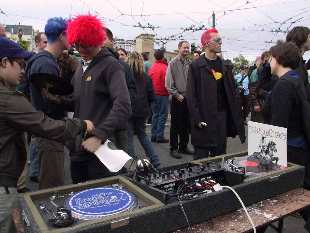 a disc jockey has set up turntables at harvey milk plaza as a crowd lingers after the award ceremony
