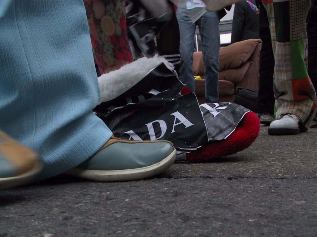 detail of reveler's footwear as the crowd fills castro street with a couch on the asphalt in the background