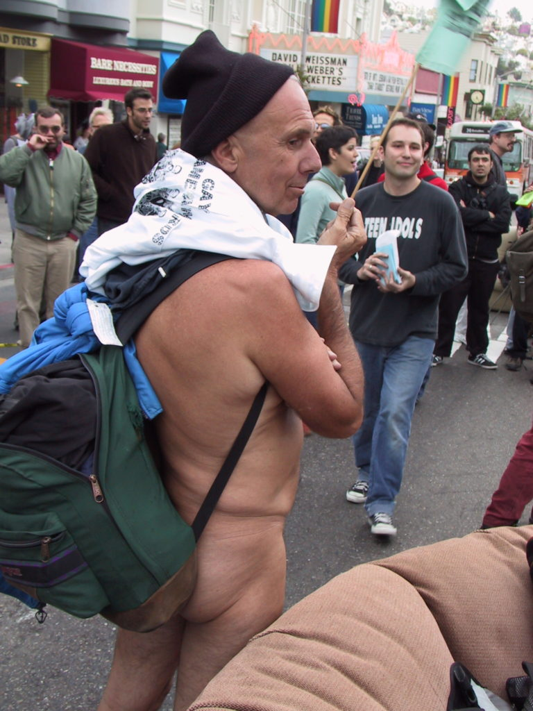 a nudist joins others milling about at castro and market after the awards ceremony blocking the muni buses