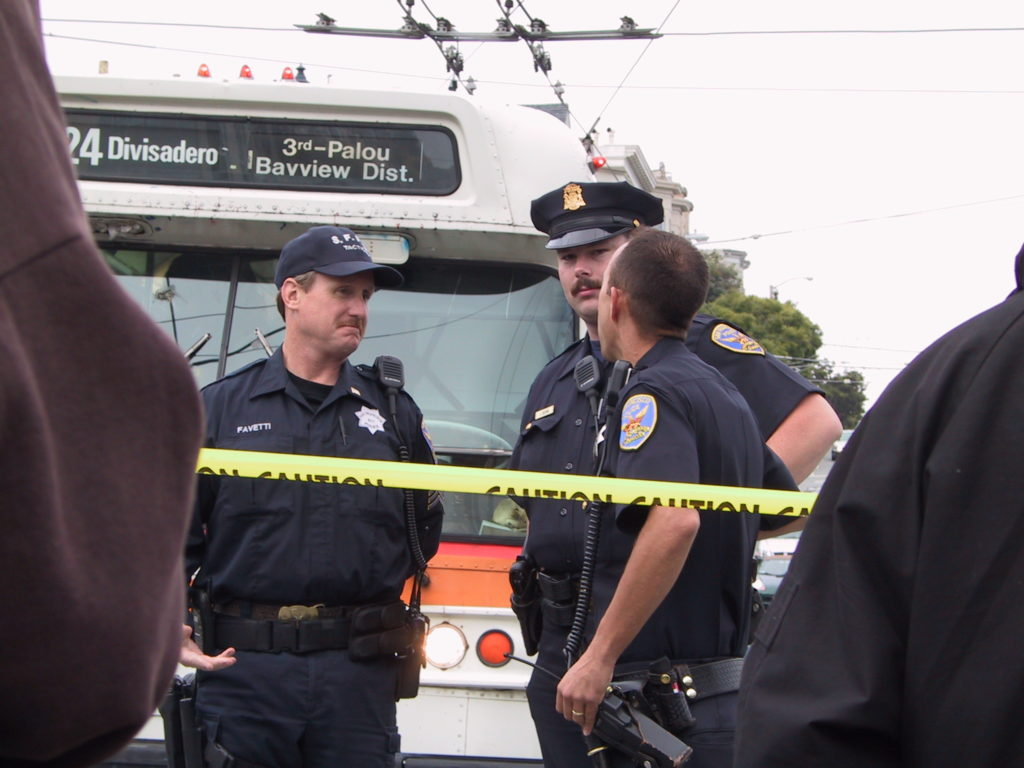 police officers stand around looking perplexed in front of a blocked 24 divisadero muni bus at castro and market behind a line of yellow caution tape