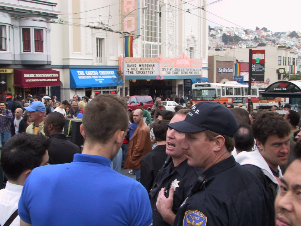 a crowd fills castro and market after the awards ceremony and two police officers complain to awards ceremony attendees