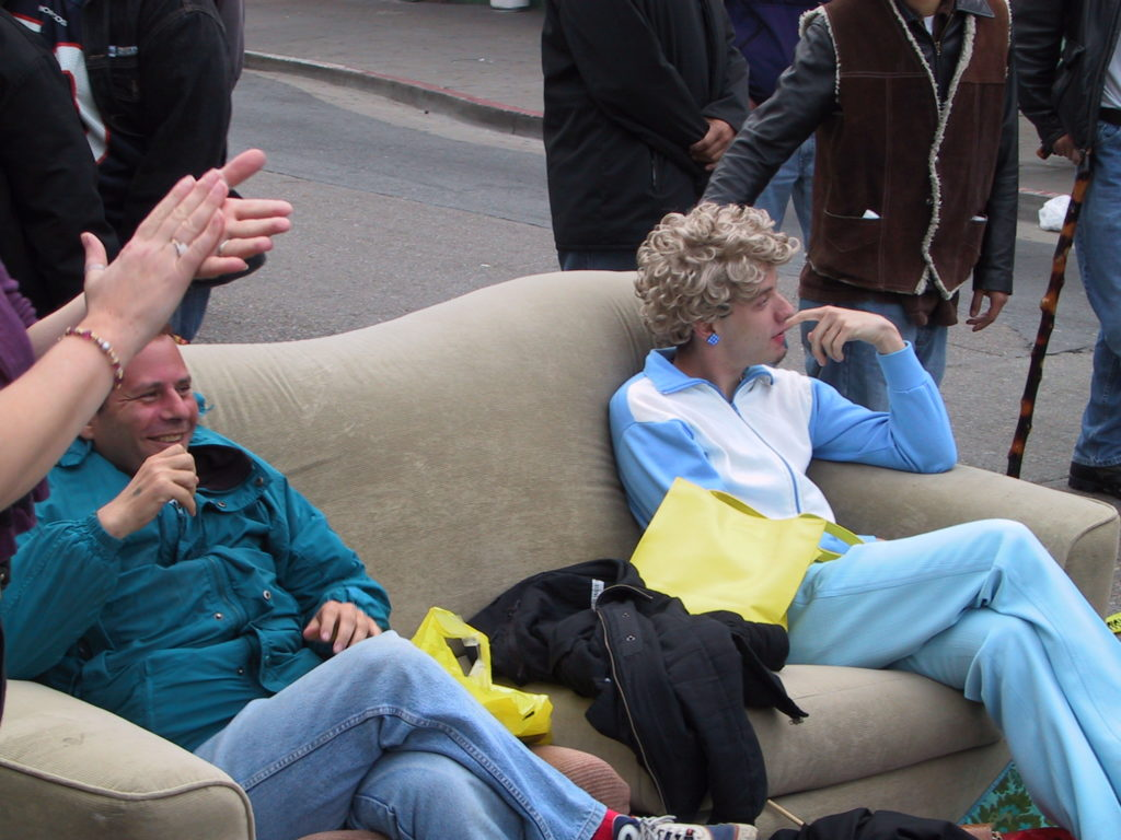 a couch has been drug out into the middle of castro street and awards ceremony attendees relax as the dance party starts up