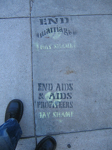 "two stencils on the sidewalk: ""end marriage -- gay shame /// end aids and aids profiteering -- gay shame"""