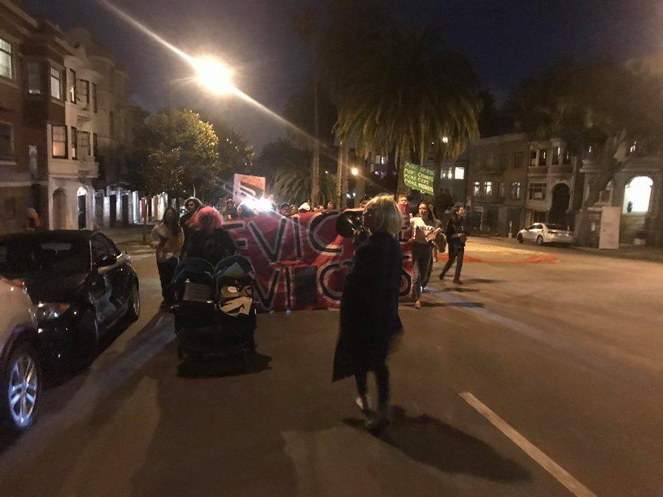 """the procession makes its way up dolores with a """"evict the evictors"""" banner out in front"""