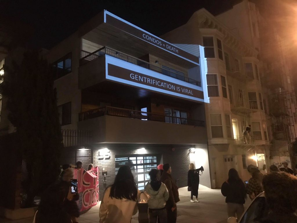 """the crowd gathers at 55 dolores with a banner reading """"EVICT THE EVICTORS"""" and a projection onto the front of the condo building that reads """"CONDOS = DEATH -- GENTRIFICATION IS VIRAL"""""""