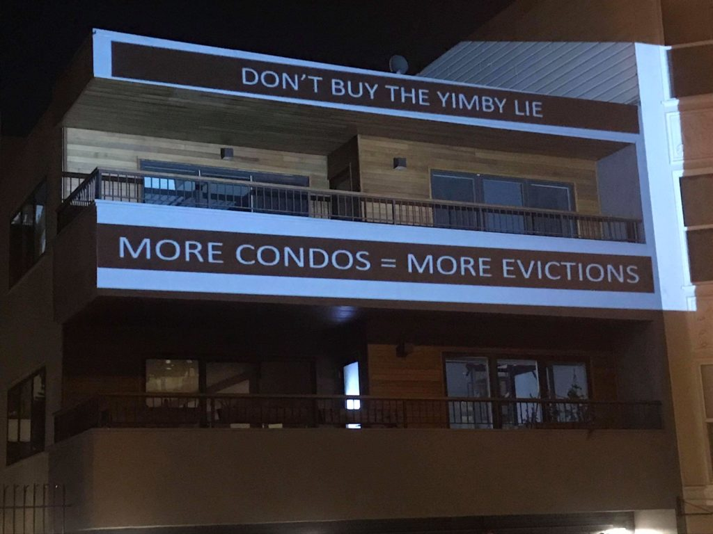 """a projection onto the 55 dolores condos that reads: """"DON'T BUY THE YIMBY LIE -- MORE CONDOS = MORE EVICTIONS"""""""