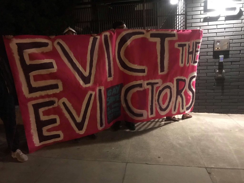 """people holding a banner at 55 dolores that reads """"EVICT THE EVICTORS"""""""