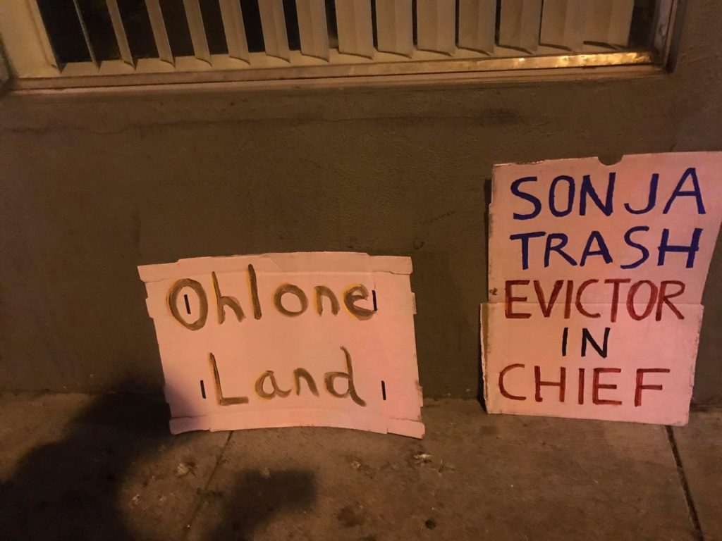 """two protest signs leaning against the wall that read: """"OHLONE LAND"""" and """"SONJA TRASH EVICTOR IN CHIEF"""""""