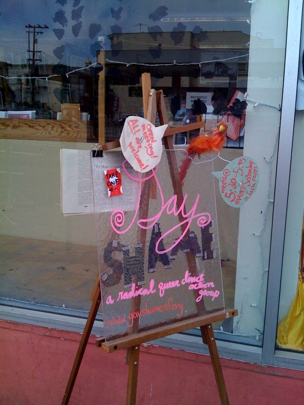 a transparent plexiglass gay shame meeting sign using pink marker with hook-and-loop-fastened pieces of carpet on an easel decorated with a fake parrot surrounded by word balloons with additional meeting details suspended on wire hangers on the sidewalk in front of modern times bookstore at 888 valencia at 20th.