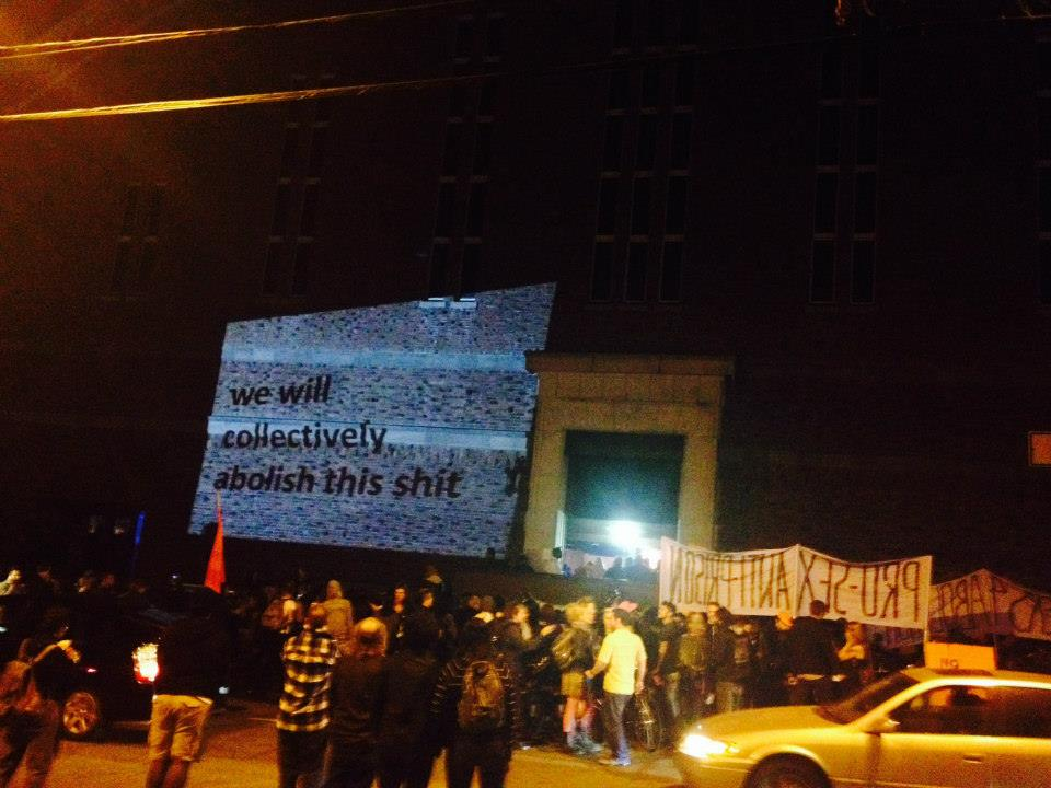 "a crowd of folks gathered in front of the north side of the armory with banners while a projection on the wall reads ""we will collectively abolish this shit"""