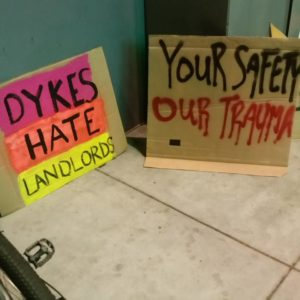 "two signs on the ground read ""dykes hate landlords"" and ""your safety our trauma"""