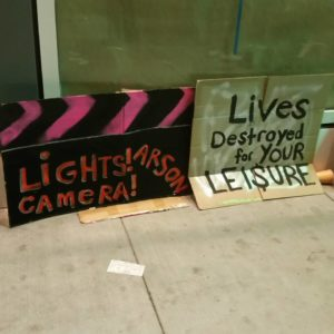 "detail of signs reading ""lights! camera! arson!"" and ""lives destroyed for your lei$ure"""