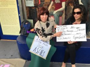 two people sit on the embankment of the hrc store with an oversized check