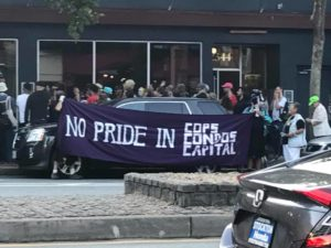 "people gather around the sidewalk in front of beaux on market to present the establishment with an award, the ""no pride in condo cops and capital"" banner in the foreground"