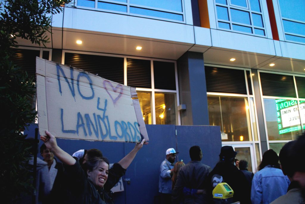 "a person hoists a ""no <3 for landlords"" signs as the vida luxury condo complex looms in the background"