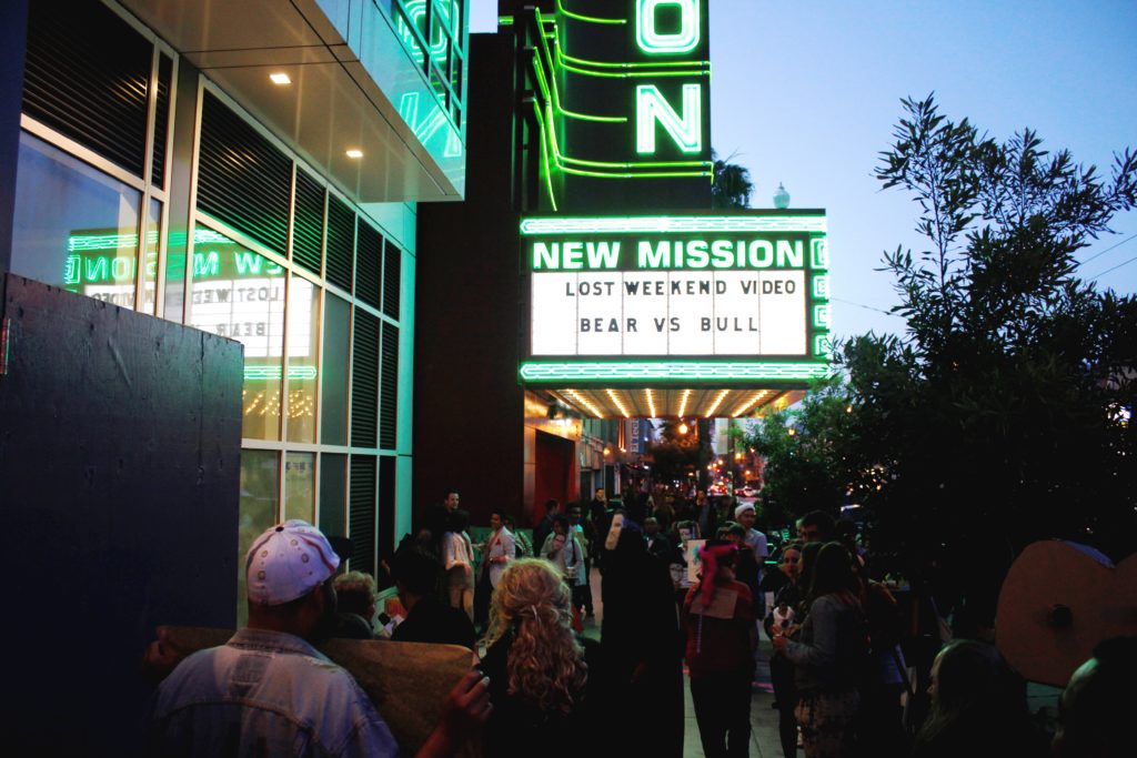 the new new mission marquee looms above the crowd gathering around the step-and-repeat in front of the vacant ground floor retail of the vida luxury condo complex on mission at 22nd