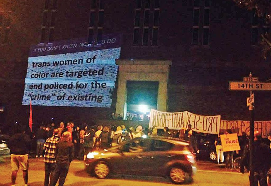 "a crowd of folks gathered by the north face of the armory holding a banner with a projection on the wall reading ""if you don't know, now you do --- trans women of color are targeted and policed for the ""crime"" of existing"