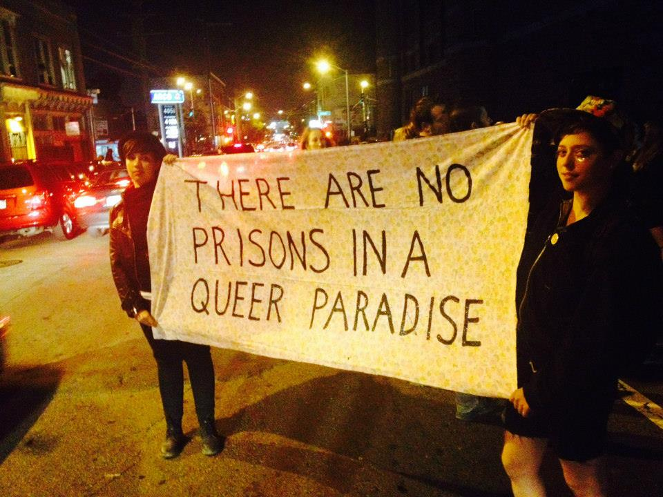 "two folks holding a banner reading ""there are no prisons in a queer paradise"""