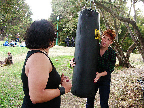 an impromptu self-defense training with a punching bag hung from a tree