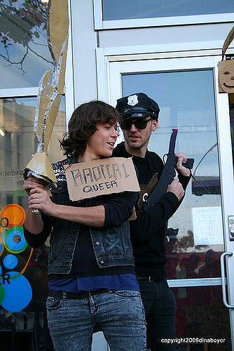 "a person dressed as a ""radical queer"" holds a cardboard sword while sharing a bit of odd-looking apparently conspiratorial banter with a person dressed as a police officer in front of the locked-open front entrance of the lgbt center at 1800 market"