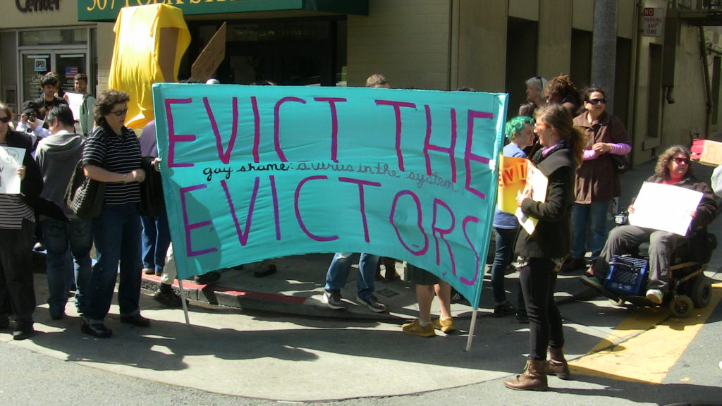 "people congregating at the street level entrance to the bornstein and bornstein office holding a baby blue banner that reads ""evict the evictors"""
