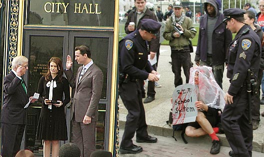 "image is two photos: one is gavin newsom being sworn in beside then wife kimberly guilfoyle-newsom by his uncle brennan; another is a person surrounded by two police officers wearing a bloodstained bridal veil holding a cardboard tombstone reading ""r.i.p. school system"""