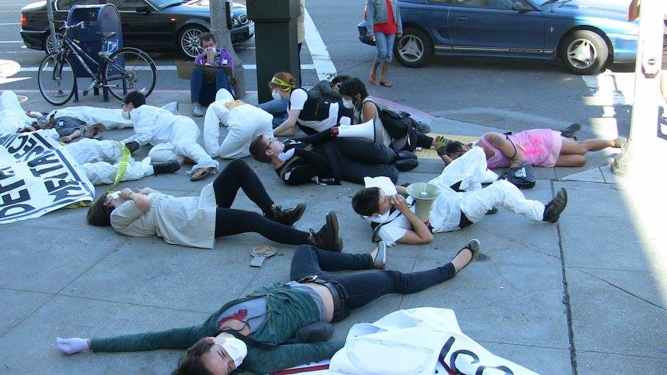 a group of people staging a die-in on the sidewalk at the corner of hayes and polk in front of the steps to the department of public health