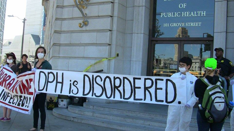 "people holding a banner in front of the department of public health that says ""dph is disordered"""